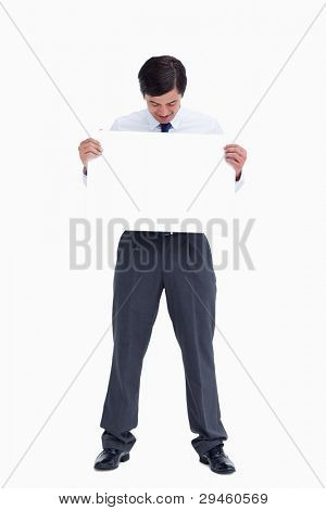 Tradesman looking at blank sign in his hands against a white background