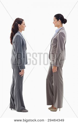 Two businesswomen smiling face to face against white background