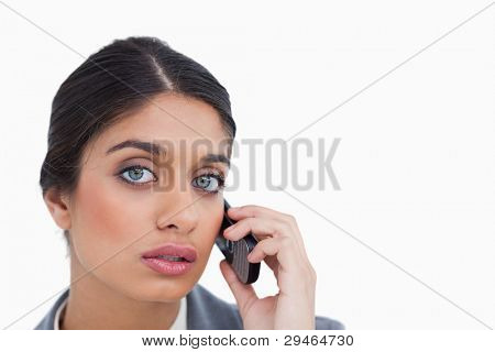 Close up of female entrepreneur listening to caller against a white background