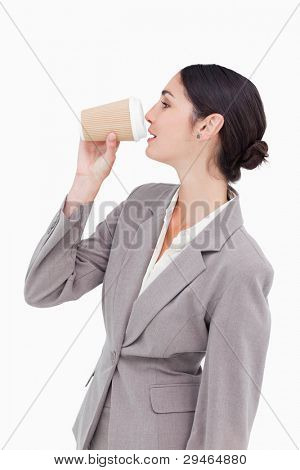 Side view of businesswoman taking a sip out of a paper cup against a white background