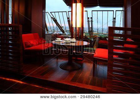 weiße Tasse, Zuckerdose und Teekanne auf Tisch, rote Sitze in leeren Restaurant am Abend