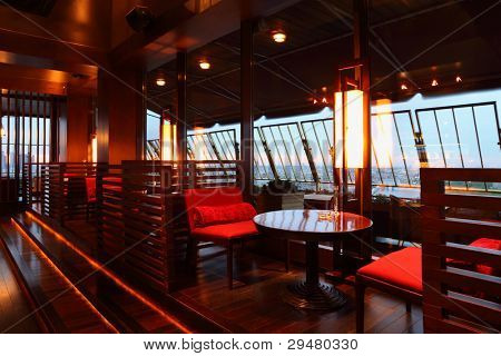 Row of brown tables and red seats with partition-walls in empty cozy restaurant at evening