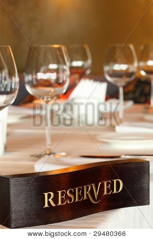 Wooden reserved plate on restaurant table with empty dishes and glasses