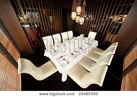 schöne Tabelle mit weißen Tischtuch und servieren und zehn weißen Stühlen im leeren restaurant
