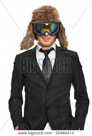 Man in ski goggles and black suit standing, isolated on white background