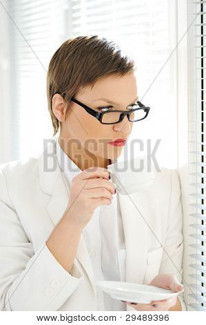 Young business woman drinking coffee while looking outside through window