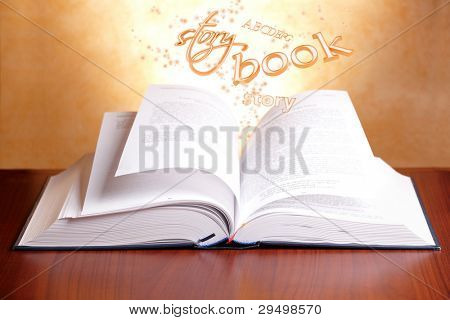 Open book laying on a table with flying words