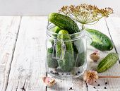 Preserved Cucumbers In Glass Jar With Dill And Garlic On  Table poster