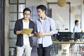 Two Young Asian Coworkers Discussing Business While Walking In Office. poster