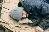 Poor Homeless Man Lying On Cardboard Outdoors poster