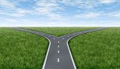 picture of symmetrical  - Cross roads horizon with grass and blue sky showing a fork in the road or highway business metaphor representing the concept of a strategic dilemma choosing the right direction to go when facing two equal or similar options - JPG