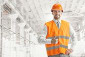 The Builder In A Construction Vest And Orange Helmet Smiling With Sign Ok Against Industrial Backgro poster