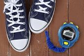 Clothes, Shoes And Sport - Top View Fragment Closeup Pair Blue Gumshoes And Stopwatch On A Wooden Ba poster