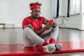 Attentive Sportive Guy Resting After Intense Training While Looking On Smartphone poster