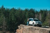 Young Man At Edge With Beautiful View Of Lake Near White Suv Car. Copy Space. Adventure Time poster