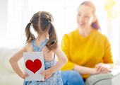 Happy mothers day! Child daughter is congratulating mom and giving her card. Mum and girl smiling.  poster