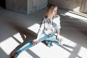 Modern Stylish Young Sexy Woman In A Fashionable Shirt In Blue Ripped Jeans In Green Cowboy Boots Si poster