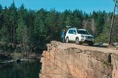 Car Travel Concept. Woman Near White Suv Car At Rock Edge Lake In The Bottom poster