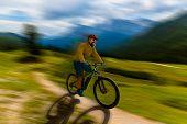 Single mountain bike rider on electric bike, e-mountainbike rides up mountain trail. Man riding on b poster
