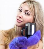 Portrait of the young blonde in fluffy mittens and with a mug poster