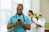 Healthcare People Group. Professional African American Male Doctor With Phone Posing At Hospital Off poster