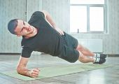 Healthy Sporty Man Doing Indoor Side Plank Exercise On Mat, Static Exercise poster