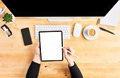 Female Hands Holding Digital Tablet And Pencil. Top View Of Wooden Office Desk With Tablet, Pencil,  poster