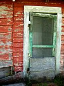 Weathered, Old Front Door Of Shabby House With Red Peeling House Siding And Green Peeling Screen Doo poster