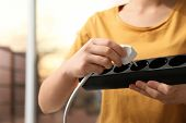 Woman Inserting Power Plug Into Extension Cord Indoors, Closeup. Electricians Professional Equipmen poster