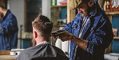 Barber With Clipper Trimming Hair Of Client, Rear View. Hipster Client Getting Haircut. Hipster Life poster
