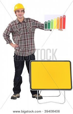 Tradesman standing before a blank sign and holding an energy efficiency rating chart