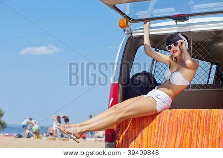 a beautiful young girl in retro look with a white swimsuit, a bandana and sunglasses