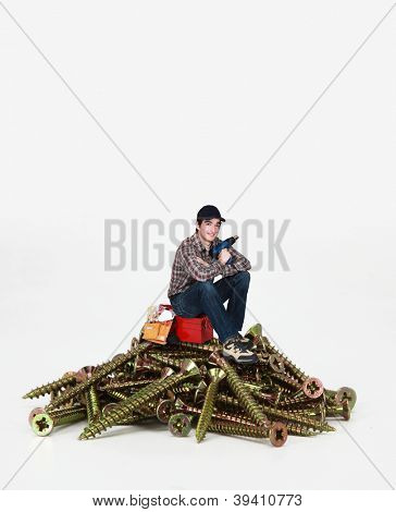 Man sitting on a toolbox and pile of giant screws