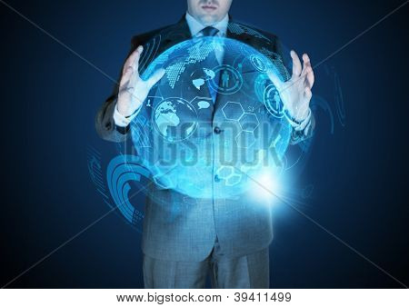 Technological Advances - A businessman holding a technical globe.