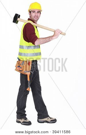 Worker carrying sledge-hammer over shoulder