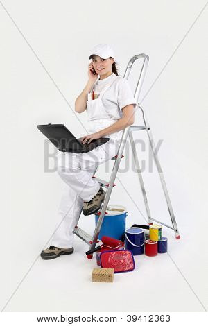 craftswoman painter working on her laptop and talking on her cell