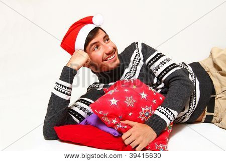 Smiling Young Man Wearing A Santa Claus Hat With Pillows Isolated On White Background