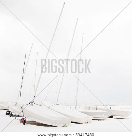 Boats Covered By Snow In A White Beach In Winter