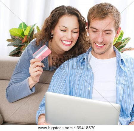 Family Shopping Online .Happy Smiling Couple Using Credit Card to Internet Shop on-line. Couple with Laptop Computer and Credit Card buying on-line. Christmas and New Year Gifts. e-shopping.ecommerce