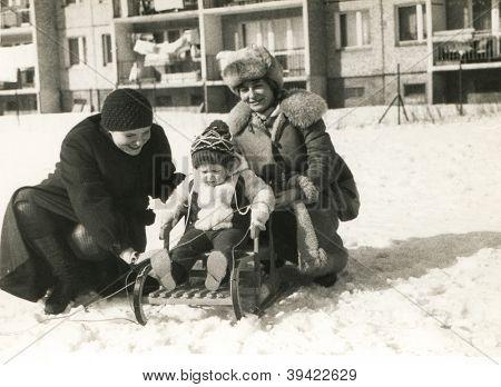 Vintage photo of mother, aunt and baby girl in winter (eighties)