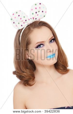 Pretty teen girl with fancy make-up and funny polka dot bow on her head looking upwards, white background