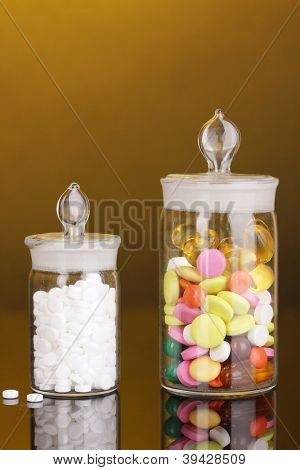 Capsules and pills in receptacles on orange background