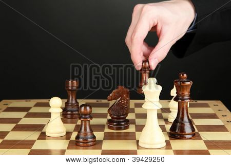 businessman playing chess isolated on black