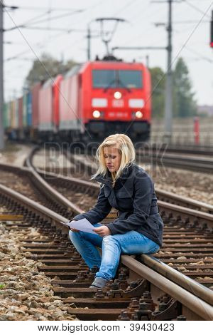 a young woman with suicidal thoughts sitting on a track. considers suicide note in his hand and thinks about her suicide.