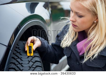 a young woman is measuring the tread depth of her car tire. the proper depth in the tread of a tire can prevent accidents.