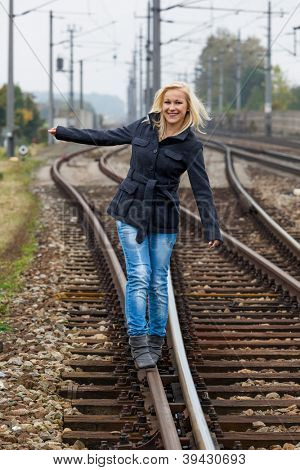 in search of the right decision, a young woman balancing on one track. life sets the course.