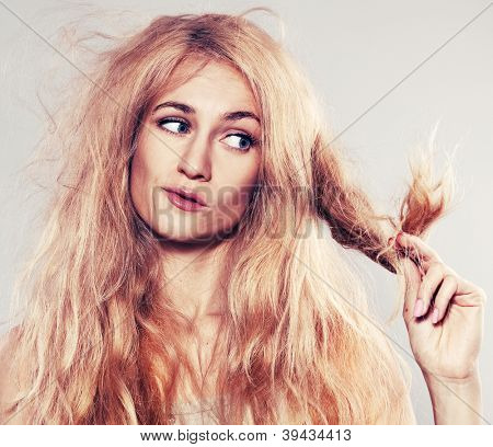 Young woman looking at split ends. Damaged long hair