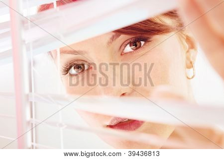 Beautiful woman are looking through jalousie, closeup