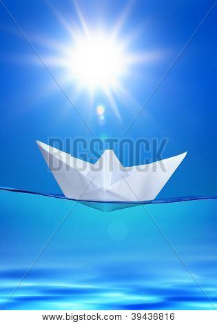 white paper toy-ship on the blue water under sun
