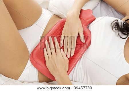 Close up of woman belly with hot water bottle in bed